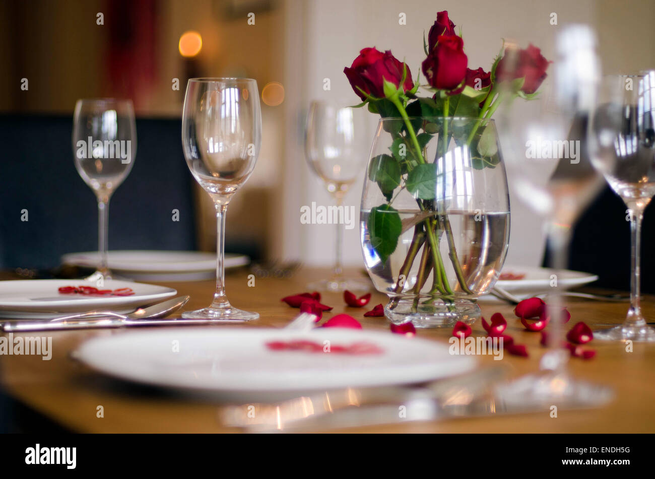 A Dining Table Set With Place Settings Wine Glasses Red Roses In - Wine glass table setting