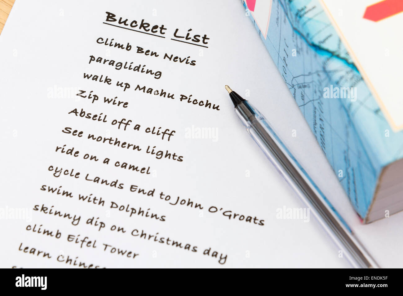An English person's to do list of ideas plans written on white note paper with a black pen and travel guide - Stock Image
