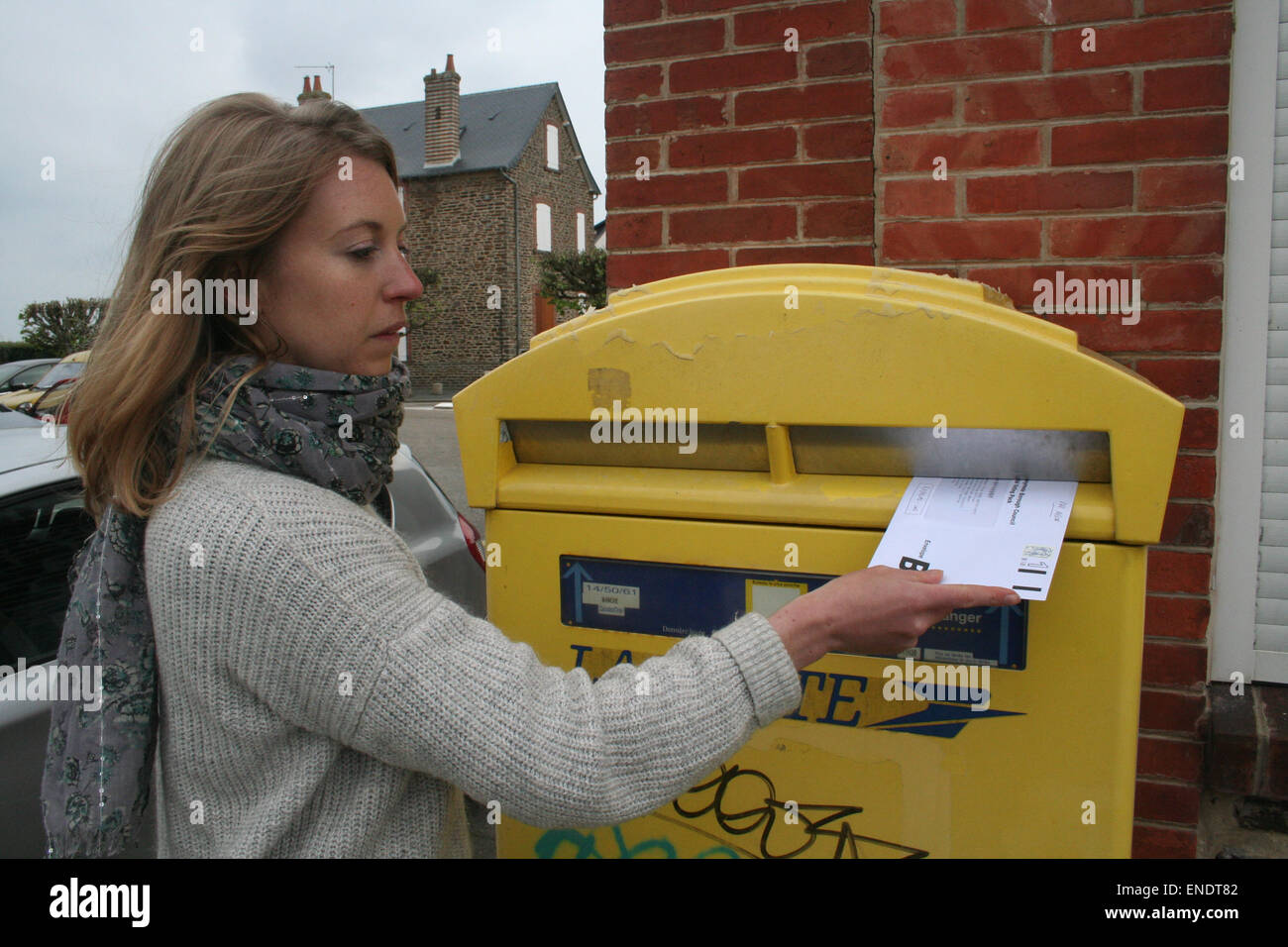 British expat, Julia White, 31, posts her postal vote in a French postbox. The vote must arrive by 10pm on 7th May - Stock Image