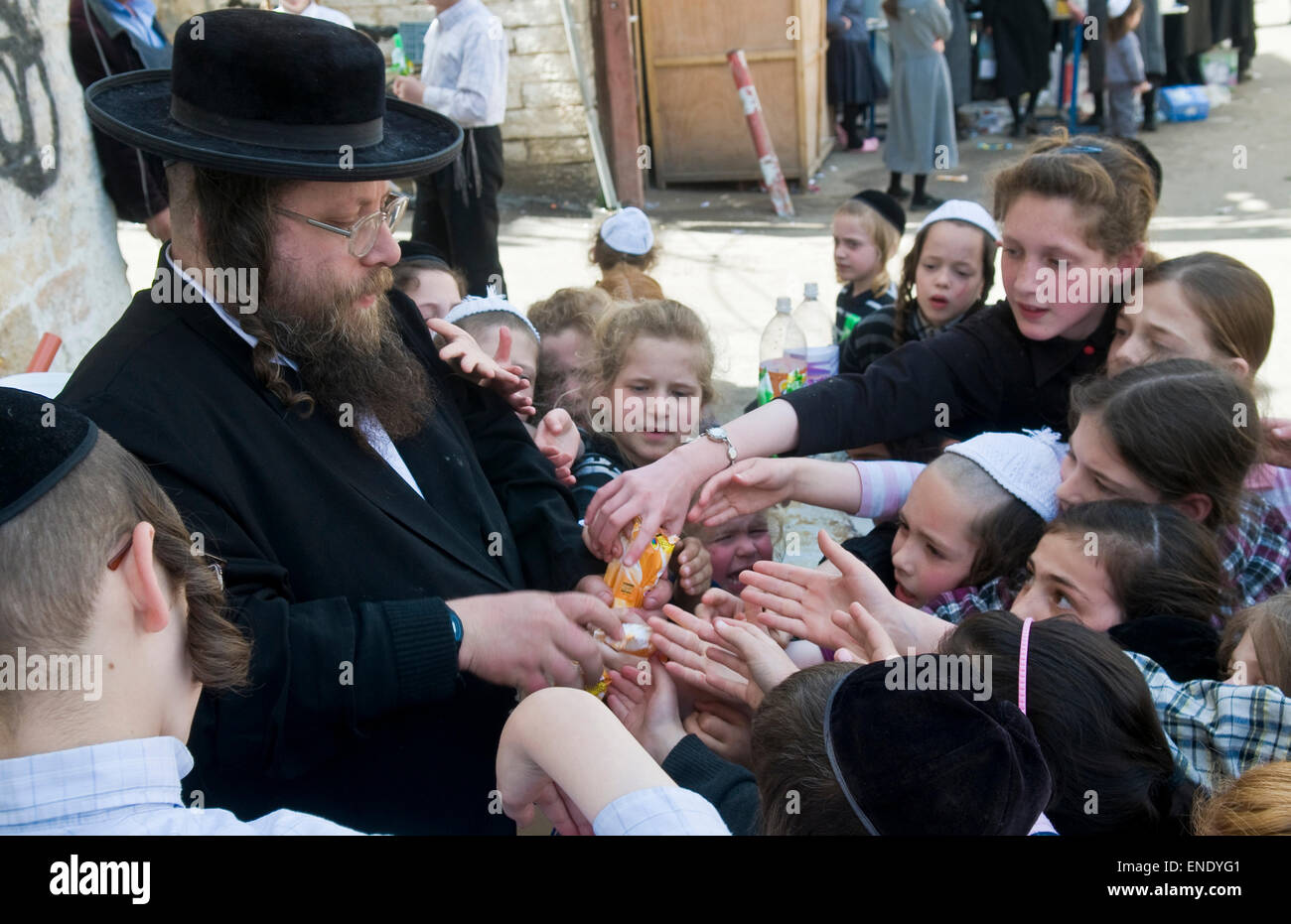 An Ultra Orthodox Jew man handing out food to poor children in Jerusalem Israel - Stock Image