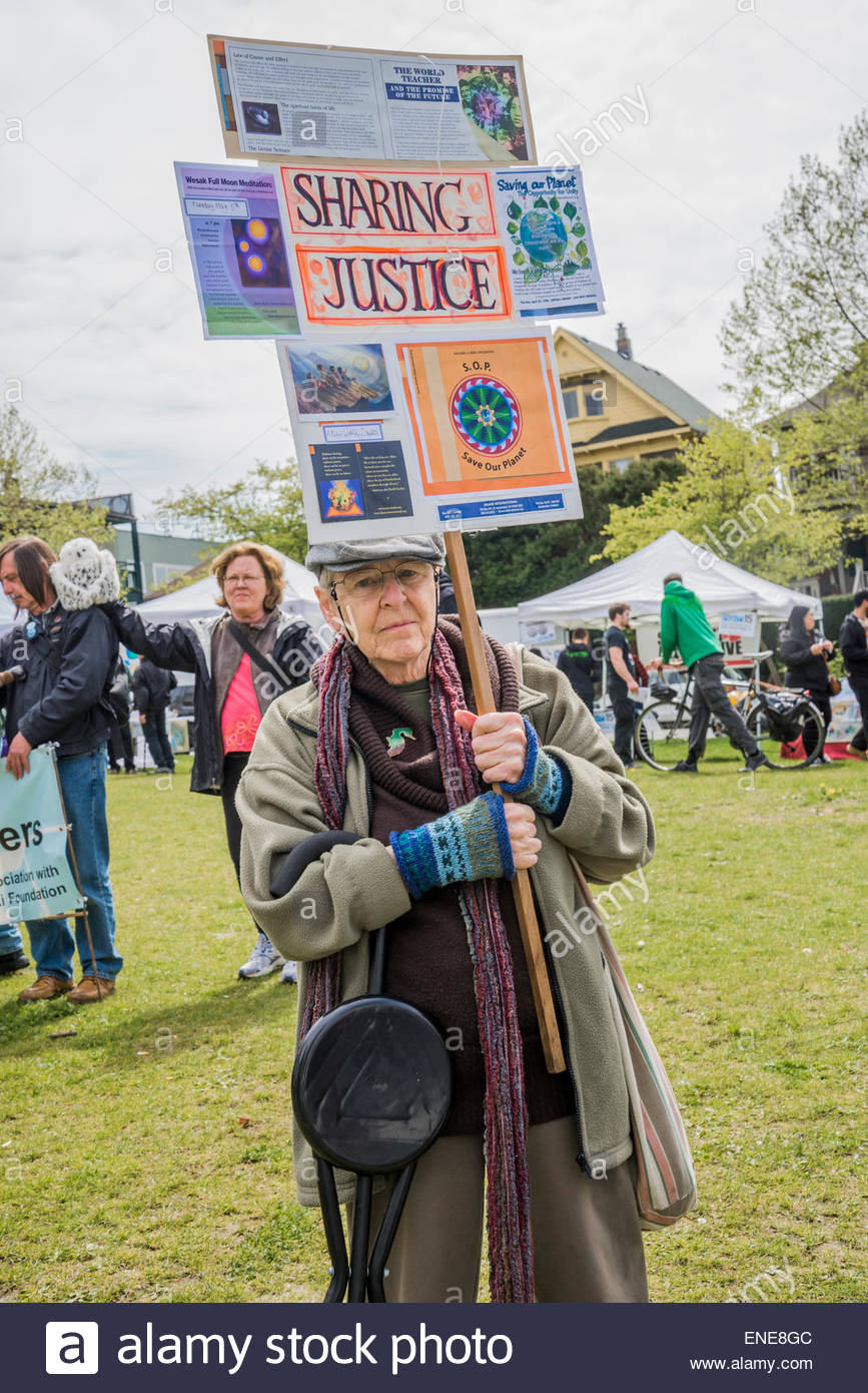 Senior with Sharing Justice sign,  2015 Earth Day Parade Commercial Drive, Vancouver, B.C. Canada - Stock Image
