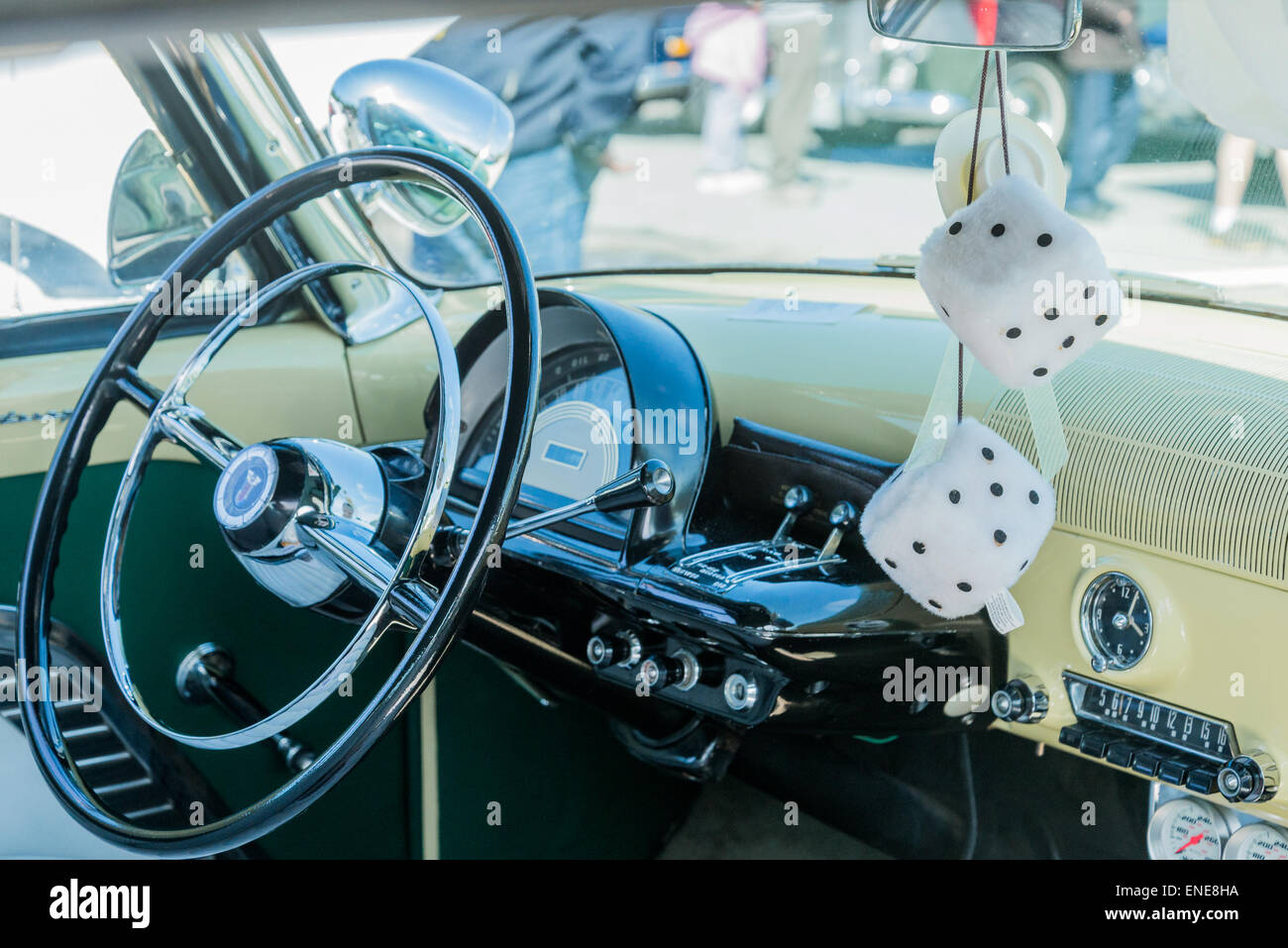 Fuzzy dice hanging from rear view mirror of classic automobile. - Stock Image