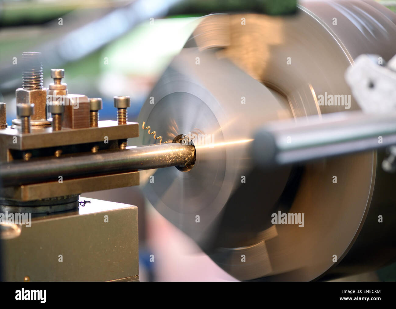 Close Up of Lathe in Operation with Focus on Spindle and Spinning Headstock and Gold Colored Shavings - Stock Image