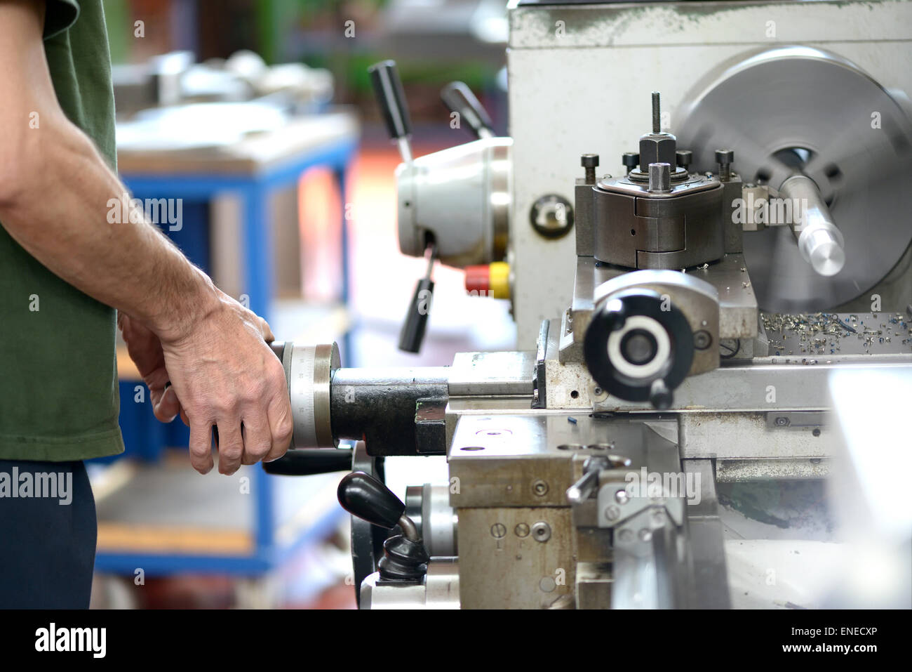 Male blue-collar worker doing manual labor with a lathe, industrial machine tool used in metalworking - Stock Image
