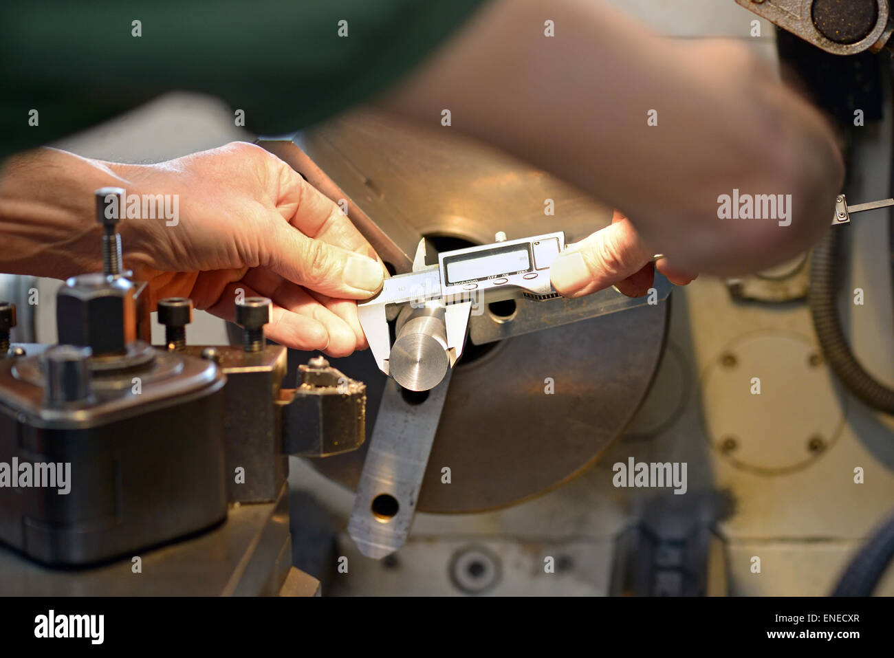 Hands of a male mechanical engineer while measuring a metallic piece with an accurate caliper, at workbench Stock Photo
