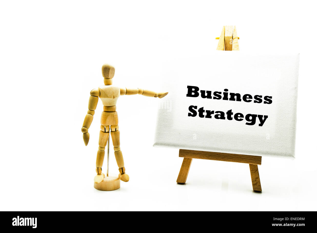 Wooden man with white board pointing at words 'business strategy' businesses strategies strategic progress - Stock Image