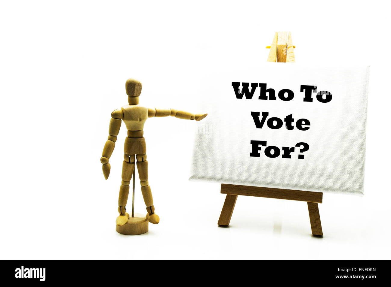 Wooden man with white board pointing at words 'who to vote for' election voting votes politics political - Stock Image