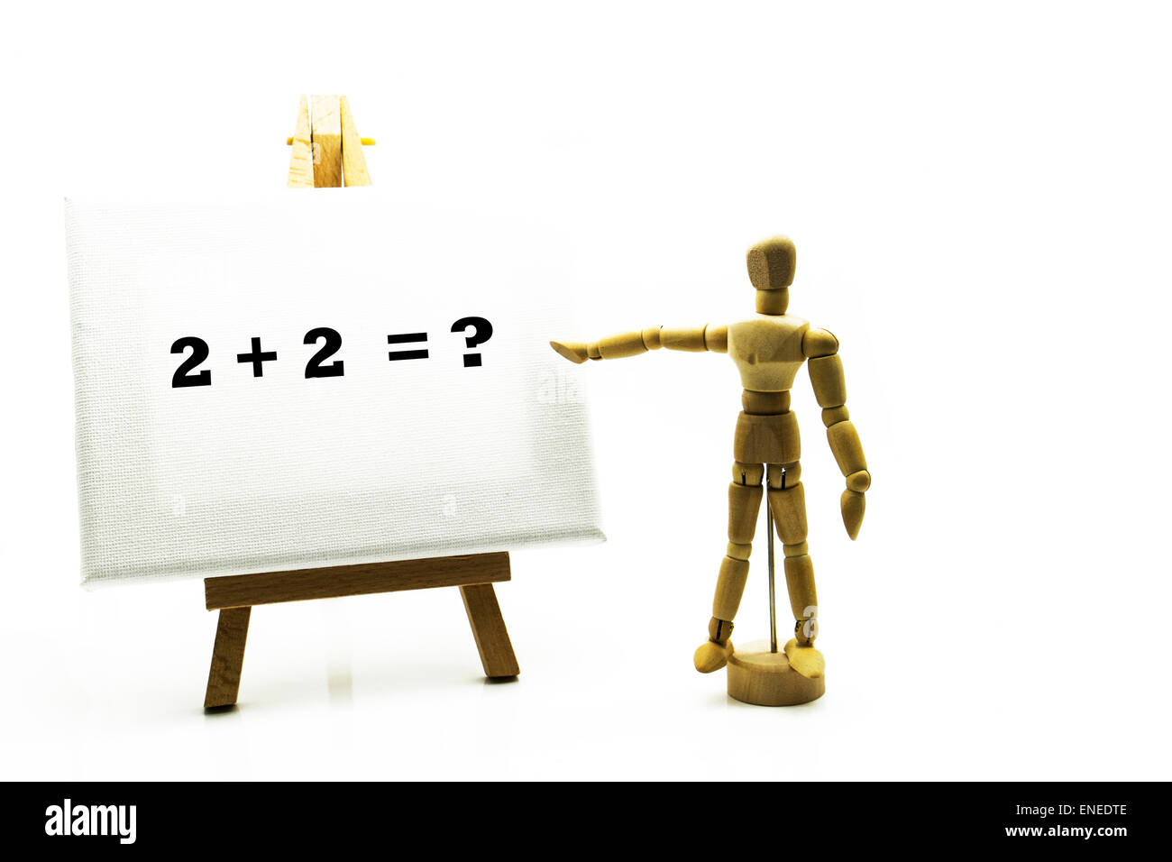 Wooden man with white board pointing at words '2 + 2 = ?' sum sums education educational concept math maths - Stock Image