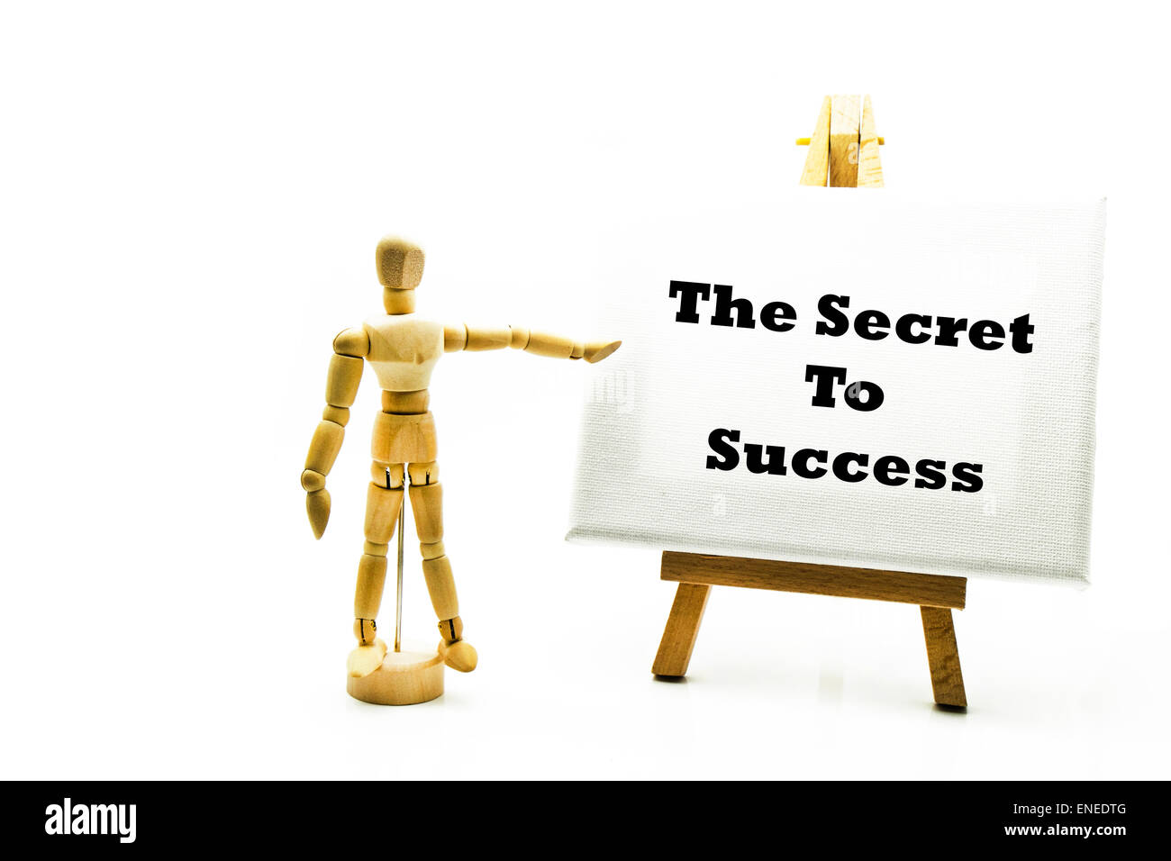 "Wooden man with white board pointing at words ""the secret to success"" secrets hidden truths hard work Stock Photo"