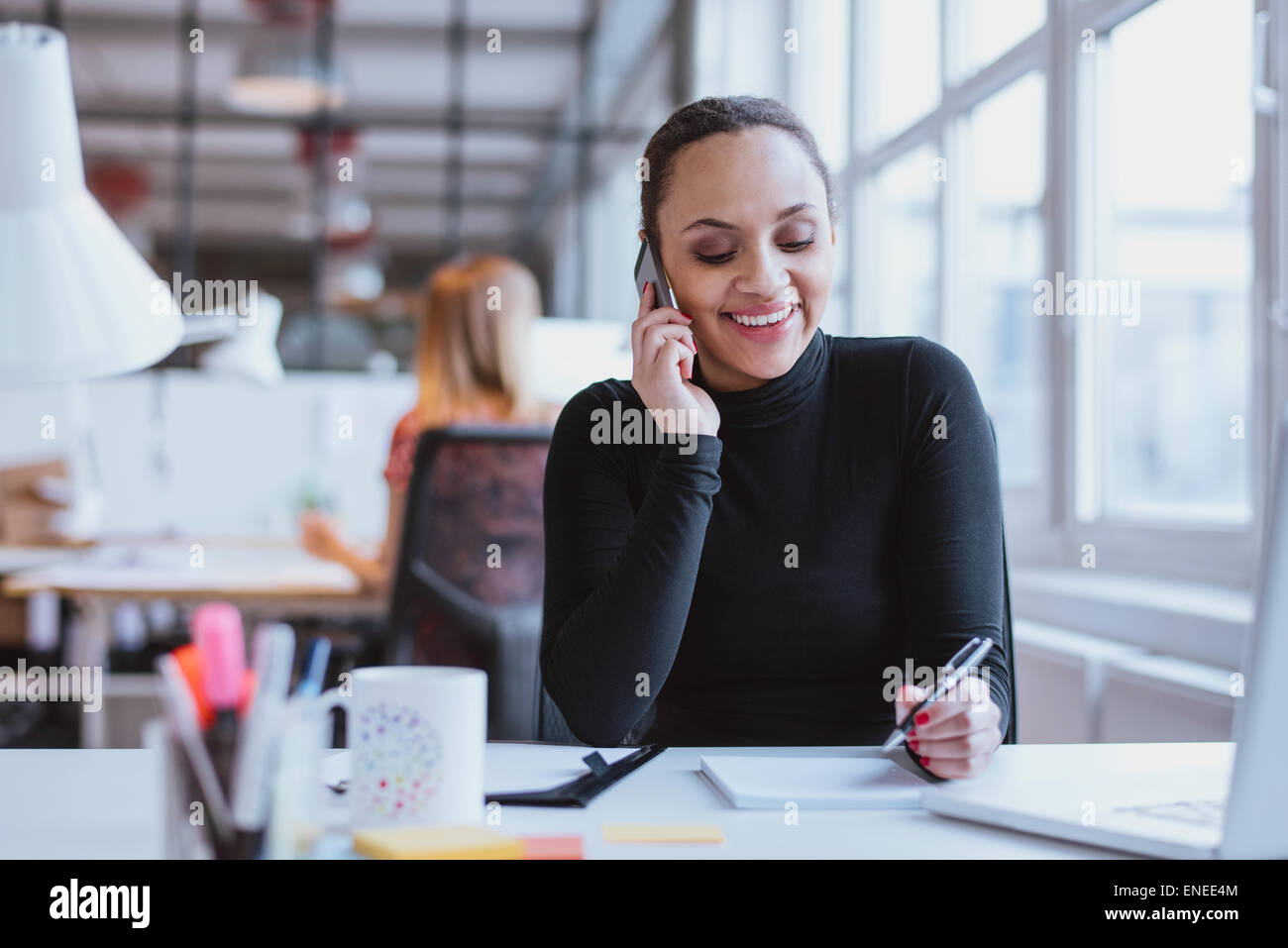 Happy young woman sitting at her desk working and answering a phone call. - Stock Image