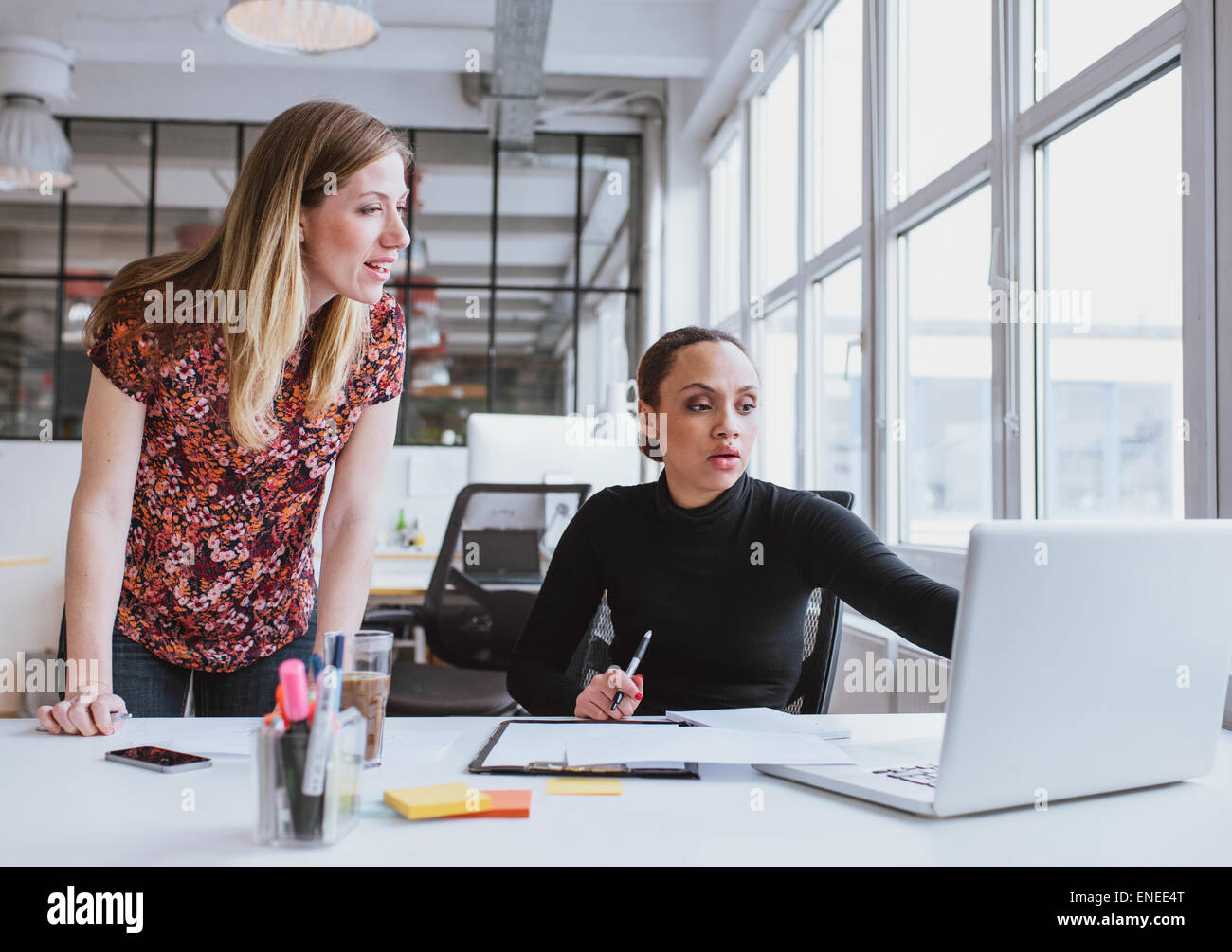 Female executives working together on new project. Creative team using laptop for information in office. - Stock Image