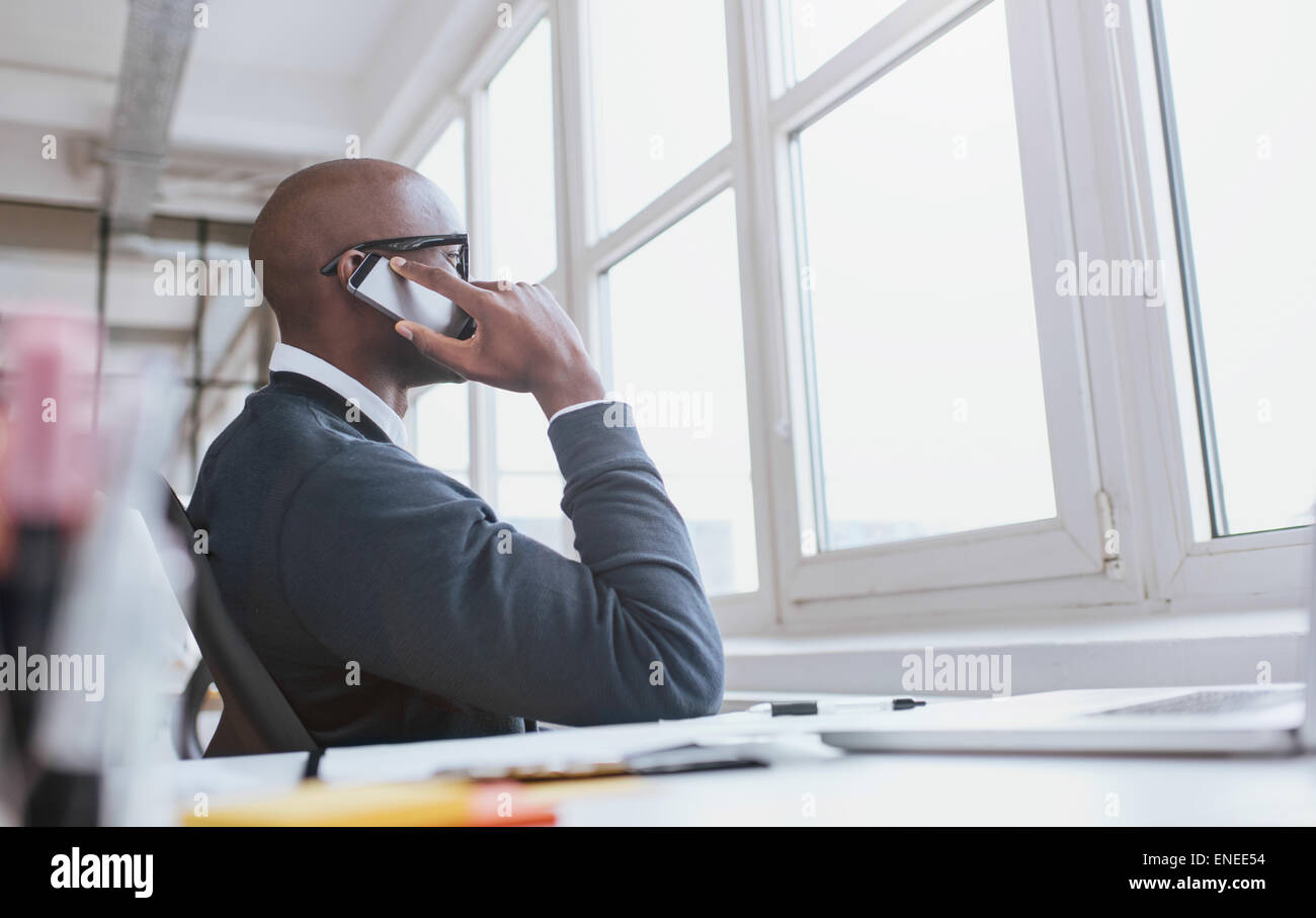 Young african man sitting at his desk talking on his mobile phone in office. African executive using cell phone - Stock Image