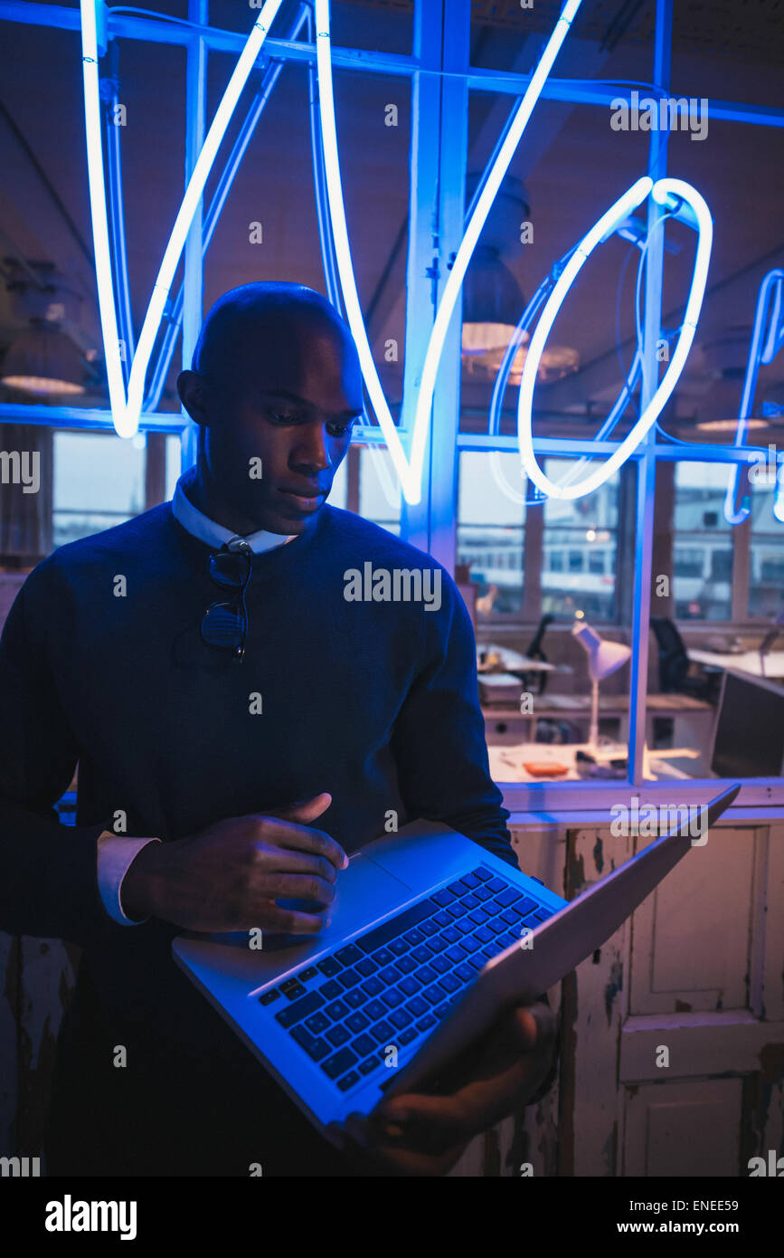 Young man in office working on laptop. African business executive standing with a laptop computer. - Stock Image