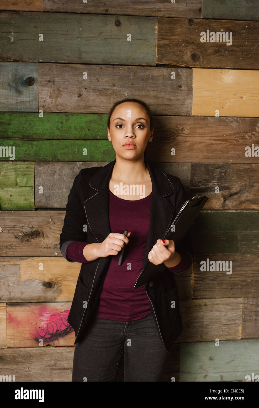 Portrait of determined young woman holding a clipboard standing against a wooden wall looking at camera. African - Stock Image