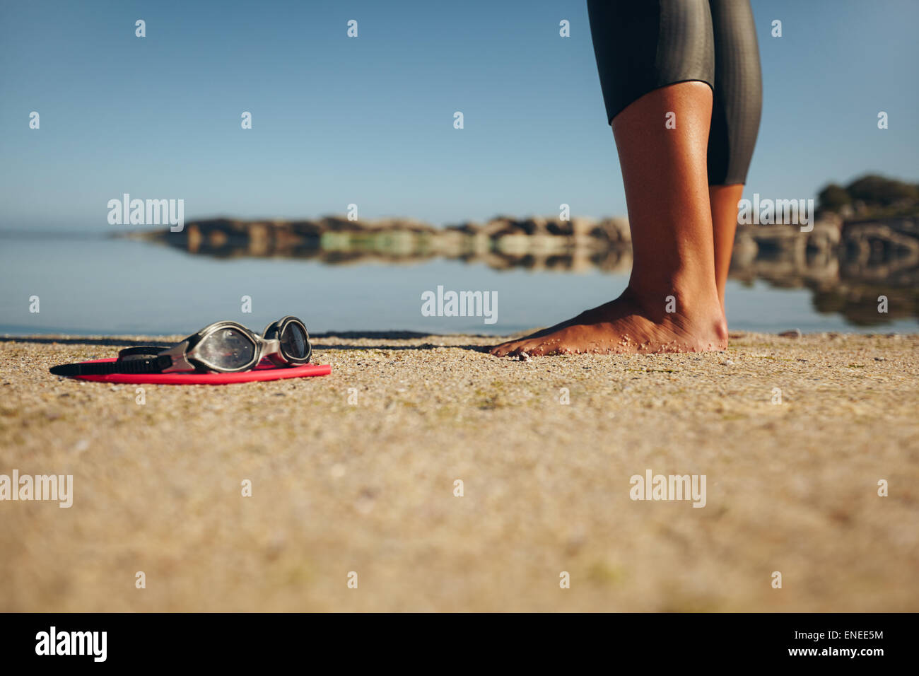 Swim goggles on the sand with feet of a woman standing by. Focus on goggles. - Stock Image