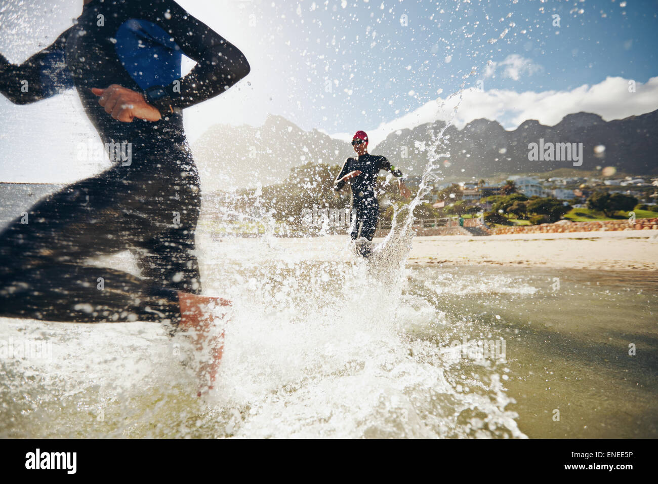 Image of triathletes rushing into the water. Athlete running into the water, training for a triathlon. - Stock Image