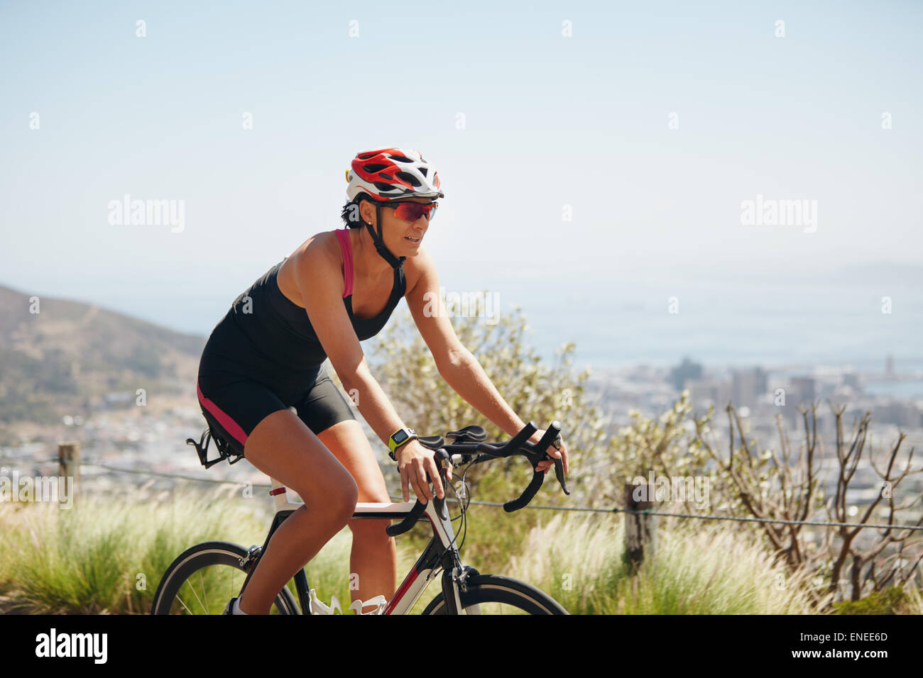 Outdoor shot of a female cyclist riding racing bicycle. Woman cycling on countryside road. Training for competition. - Stock Image