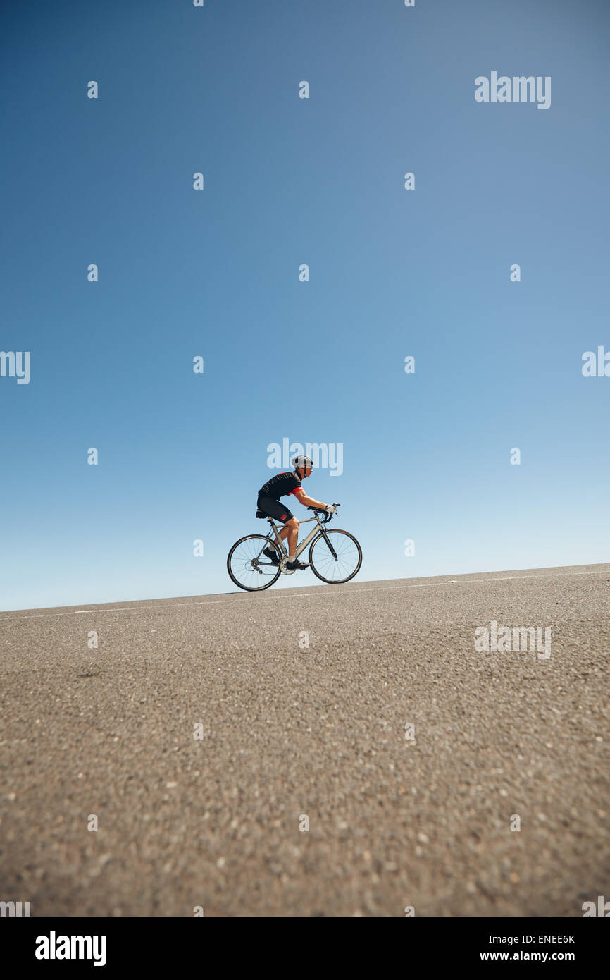 Image of male cyclist riding bicycle up hill. Athlete training for cycling event of a triathlon competition. - Stock Image