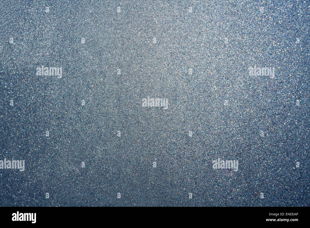 Abstract glittering silver and blue dust or sand background with blur edges of image - Stock Image