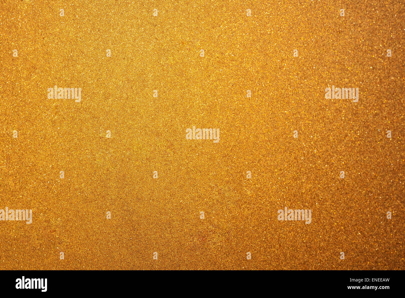 Abstract glittering golden or yellow dust or sand background with blur edges of image - Stock Image