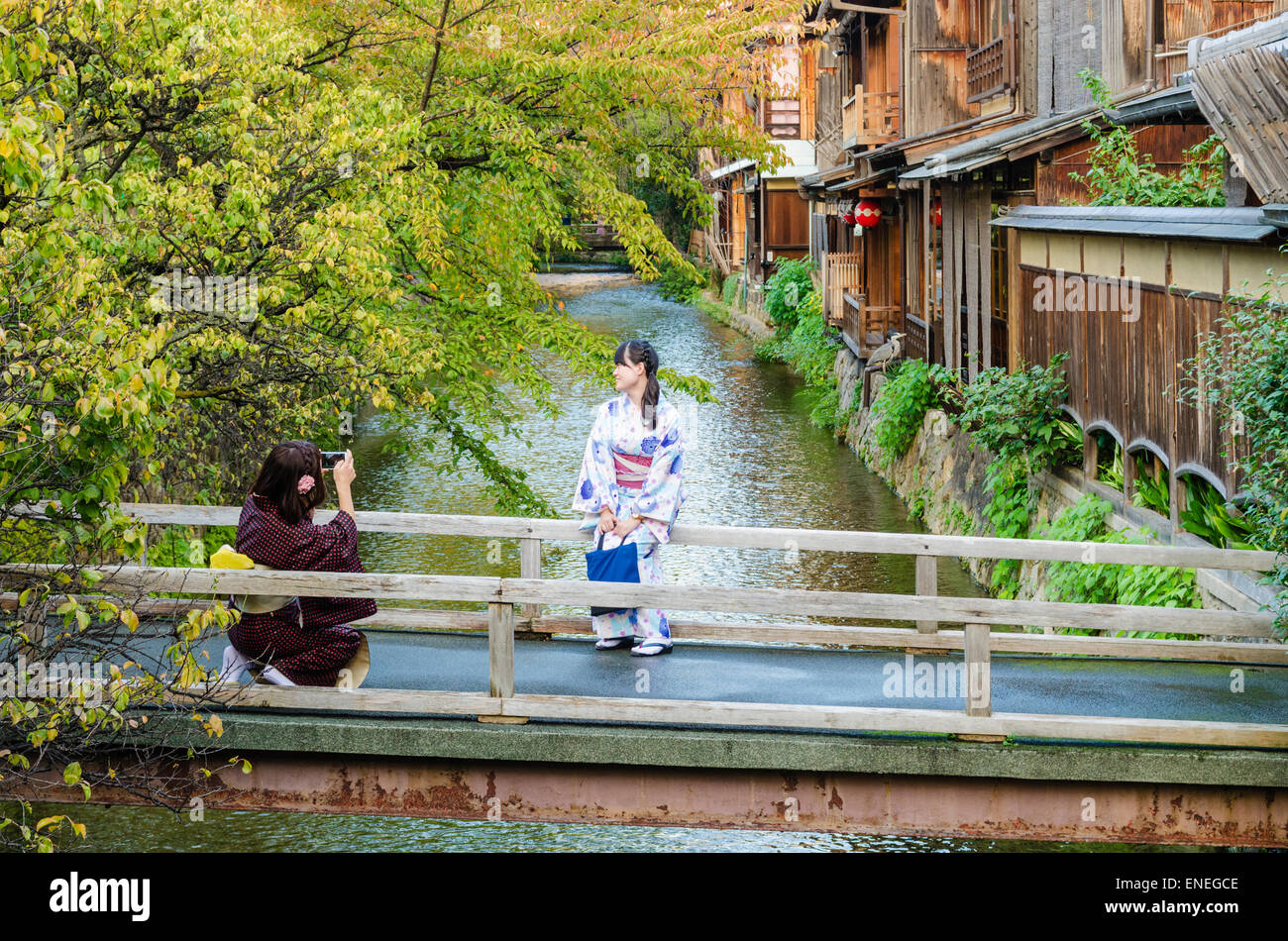 Traditionally dressed Japanese women taking photos of each other in the Shirakawa Area of Gion, Kyoto, Japan - Stock Image