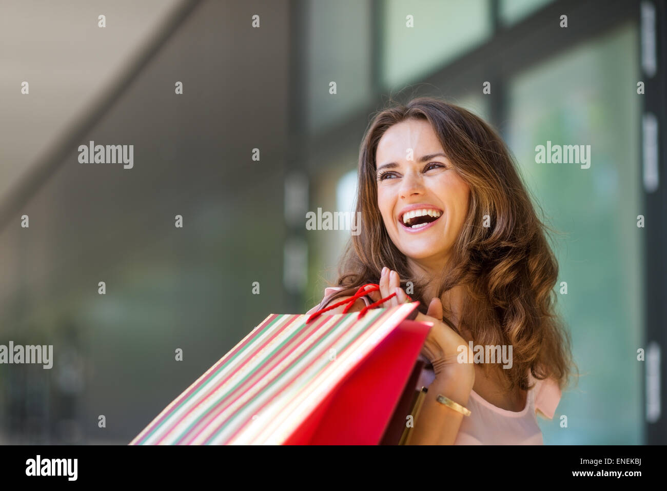 A brown-haired woman holding a striped, multi-coloured shopping bag over her right shoulder laughs and smiles while - Stock Image