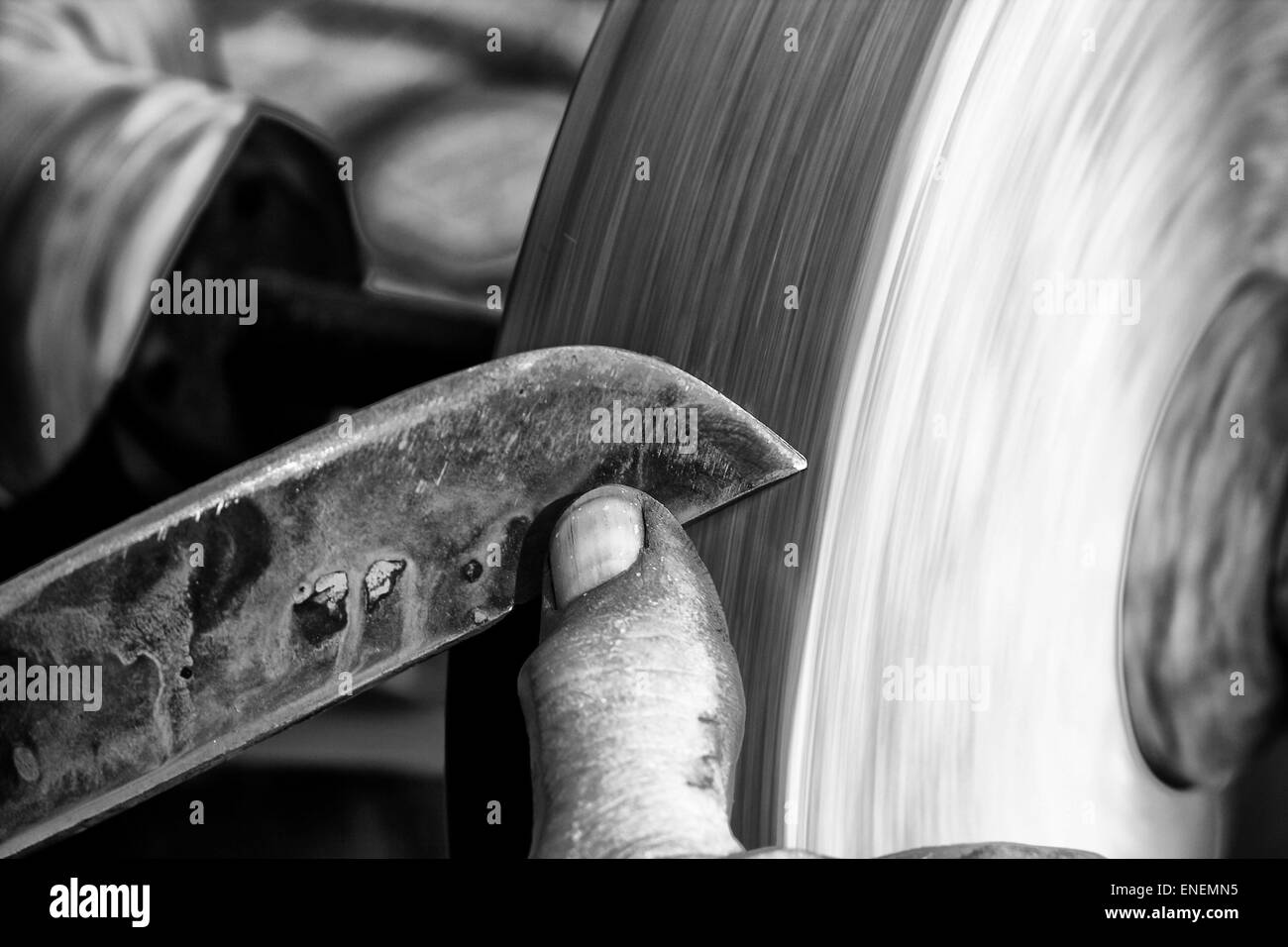 Sharpening a knife blade on a wet sandstone grinding wheel - Stock Image