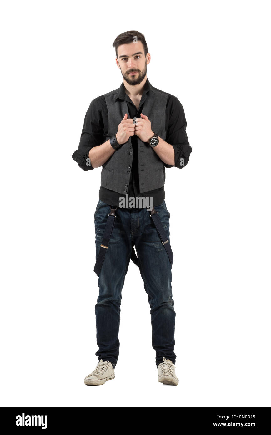 Young confident hipster holding his vest looking at camera. Full body length portrait isolated over white background - Stock Image