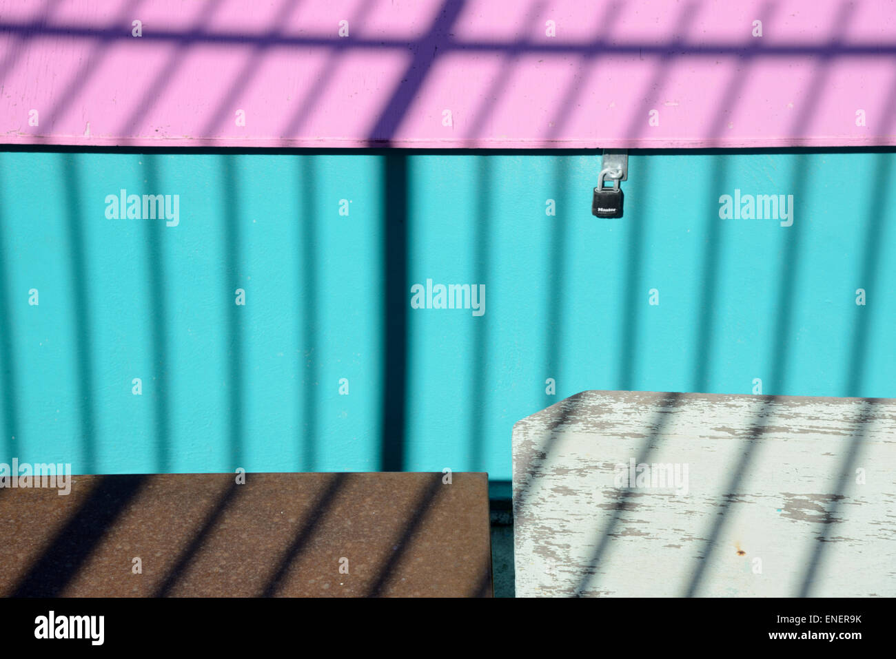 Colourful Turquoise & Pink Sheds & Shadow of Railings - Stock Image