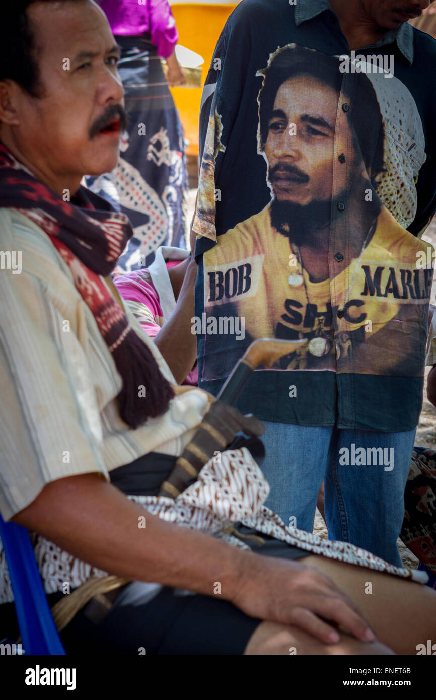 Man wears Bob Marley shirt among fellow who wears traditional clothes and accessories. - Stock Image