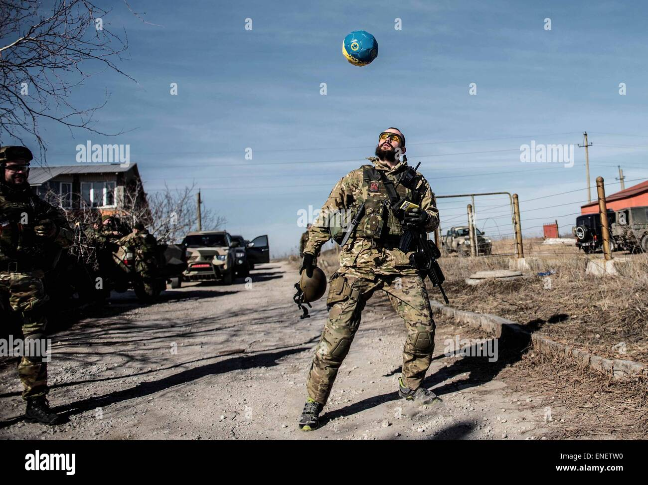 A fighter from the Azov battalion plays football near the front line in Shyrokine, ukraine. - Stock Image
