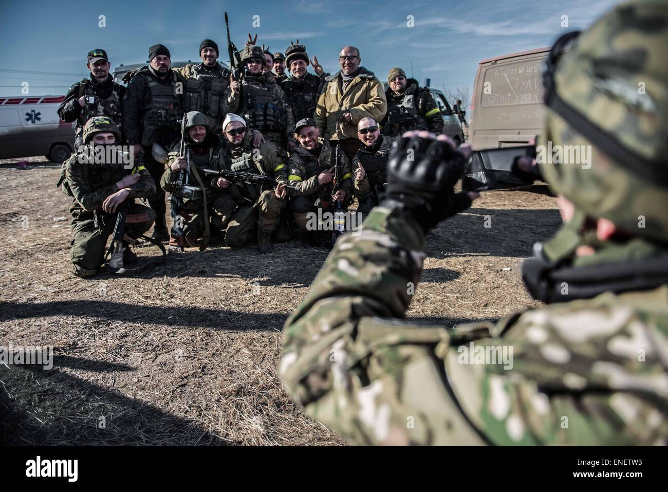 volunteer fighters with the Donbas Battalion take a photo near the front line in Shyrokine. - Stock Image