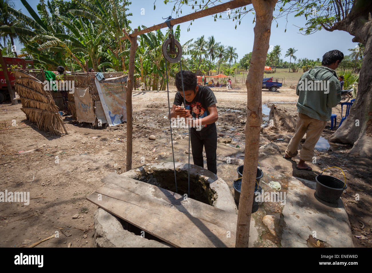 A villager lifting water from a communal water well during dry season in Sumba Island, Indonesia. - Stock Image