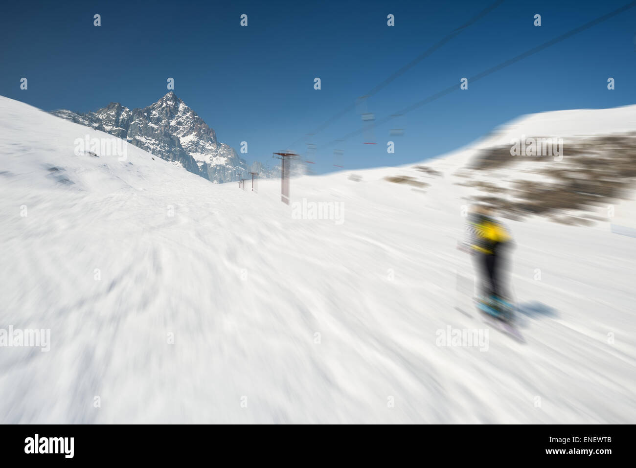 Skiing on snowy slope in scenic ski resort of the italian Alps, with bright sunny day of spring season and high - Stock Image