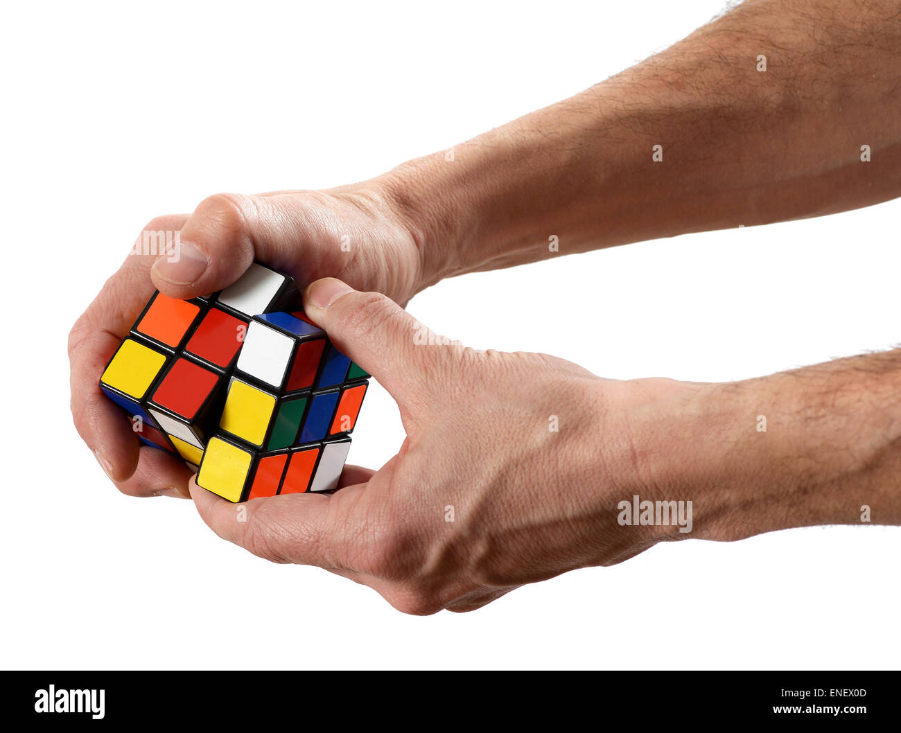 Man twisting a Rubik's cube puzzle with scrambled colors - Stock Image