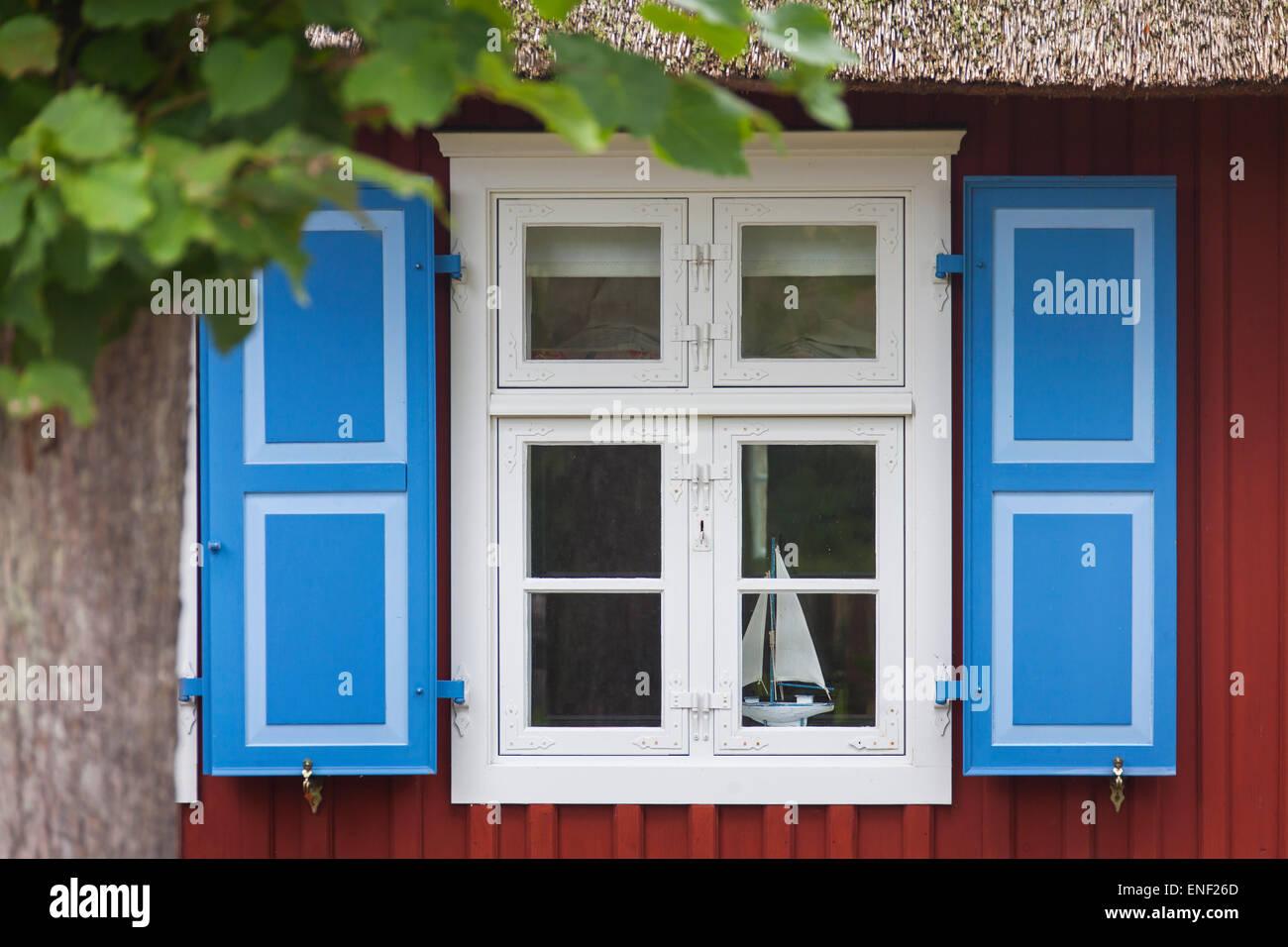 Colourful window shutters of thatched cottage at the village Born auf dem Darß, Mecklenburg-Vorpommern, Germany - Stock Image
