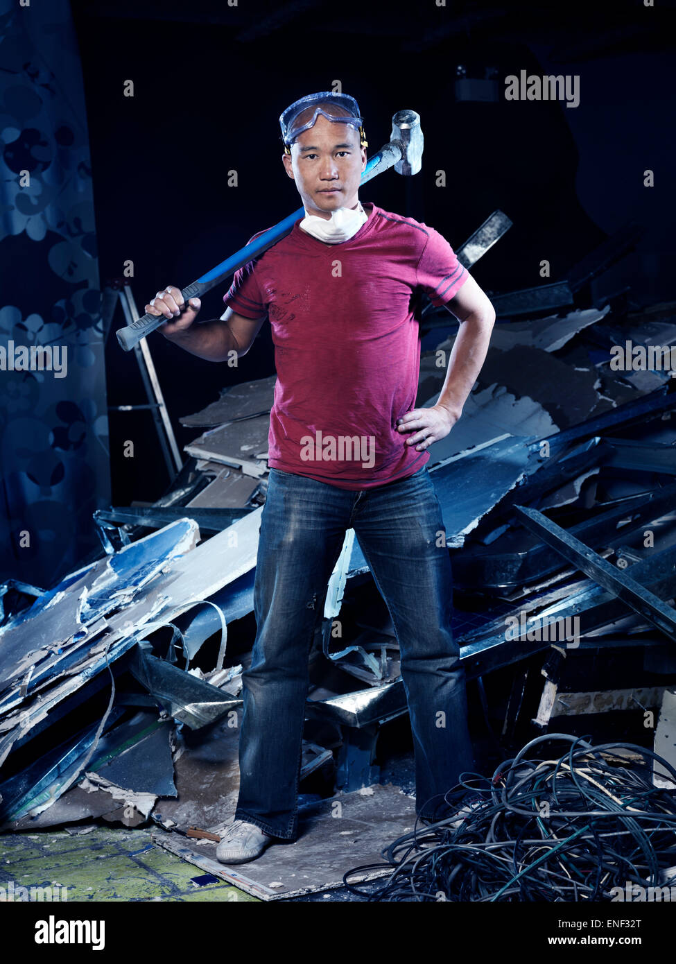 Portrait of a man with a sledgehammer doing renovations and demolition - Stock Image