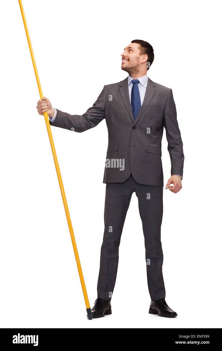 smiling man holding flagpole with imaginary flag - Stock Image
