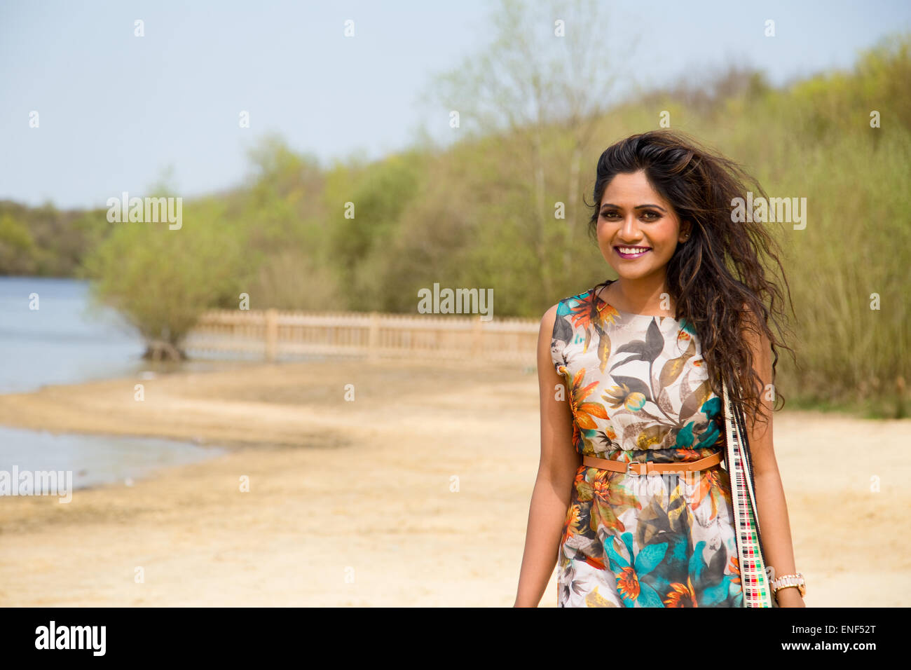young indian woman walking along the bank of the lake - Stock Image