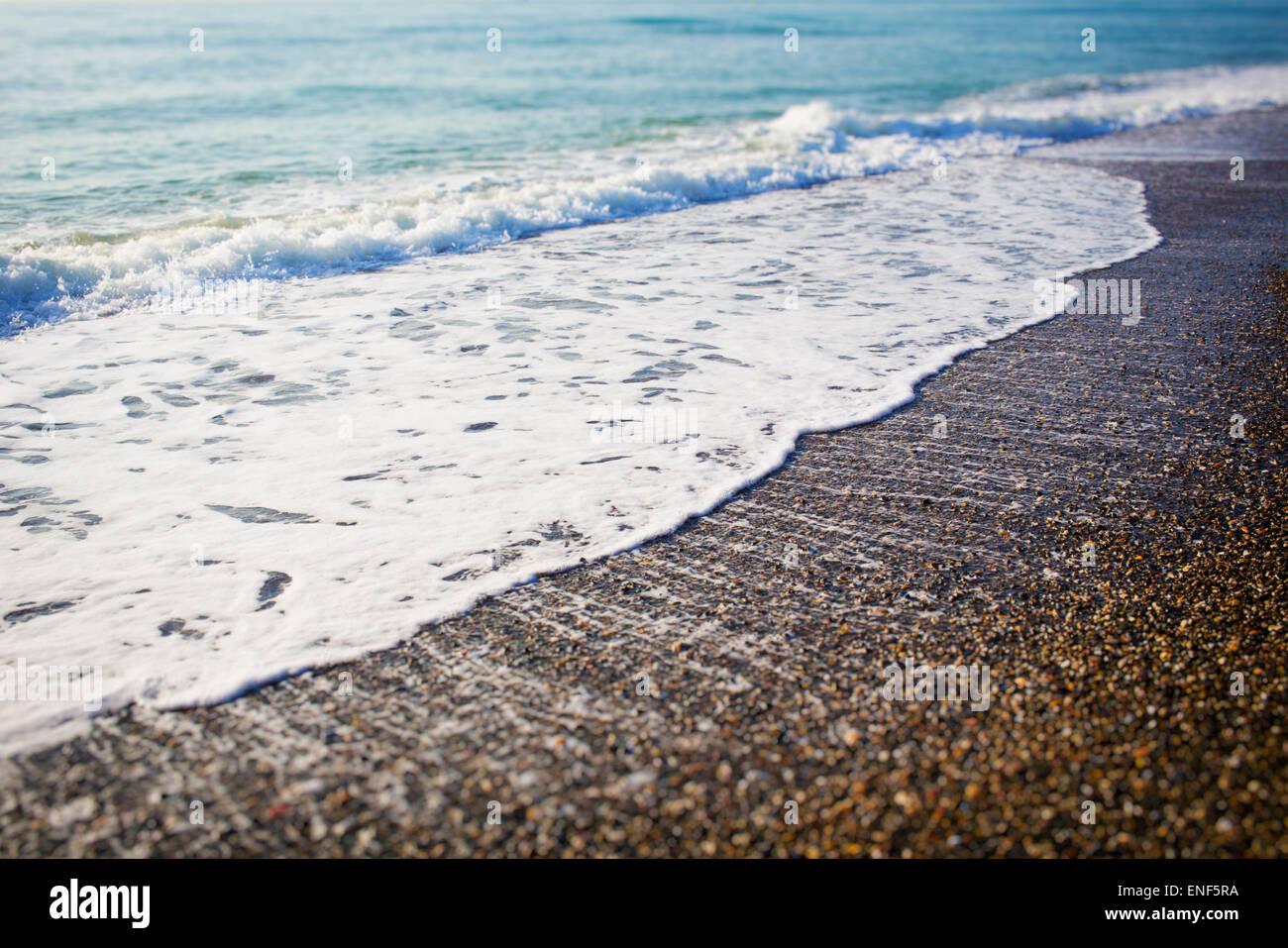 Waves breaking on seashore. - Stock Image