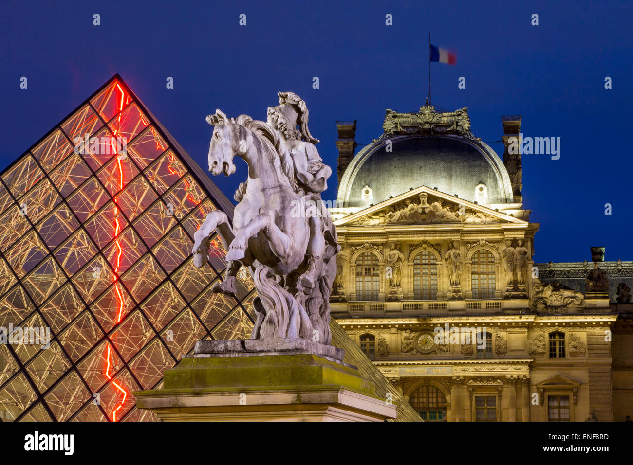 Twilight over Louis XIV Statue, the glass pyramid and Musee du Louvre, Paris, France - Stock Image