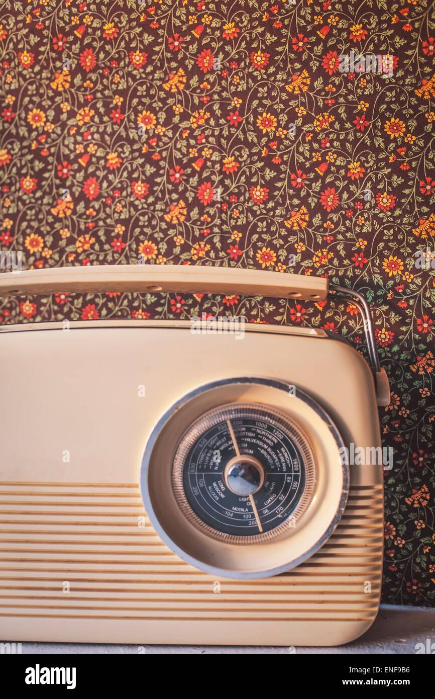 Vintage Radio with old-fashioned patterned wallpaper in the background - Stock Image