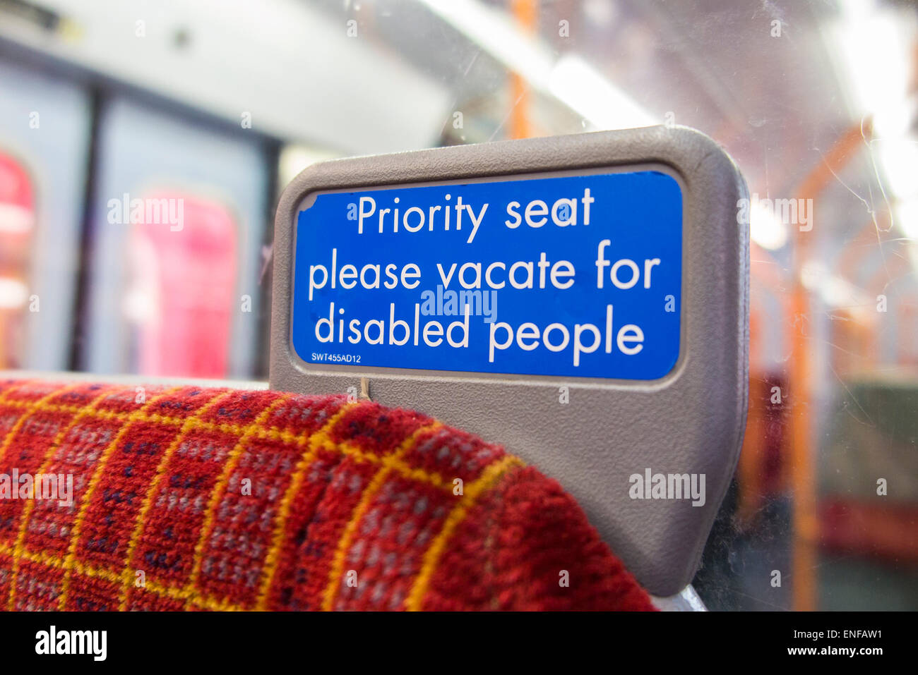 Sign on South West Trains railway carriage seat:  'Priority seat please vacate for disabled people' - Stock Image