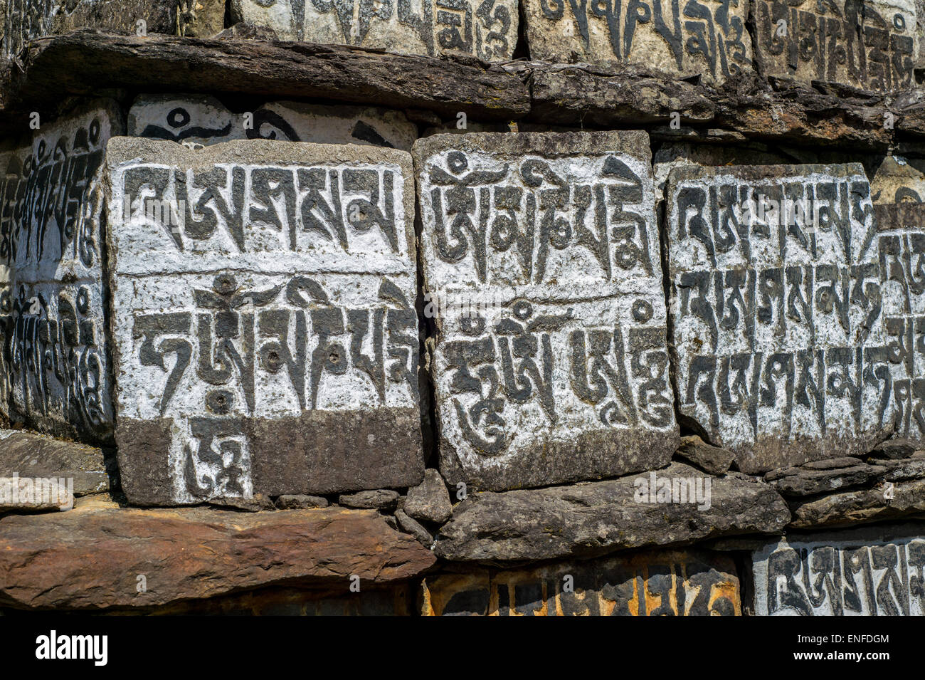 Old Mani Stones inscribed with a Buddhist mantra in the Himalaya region, Nepal - Stock Image