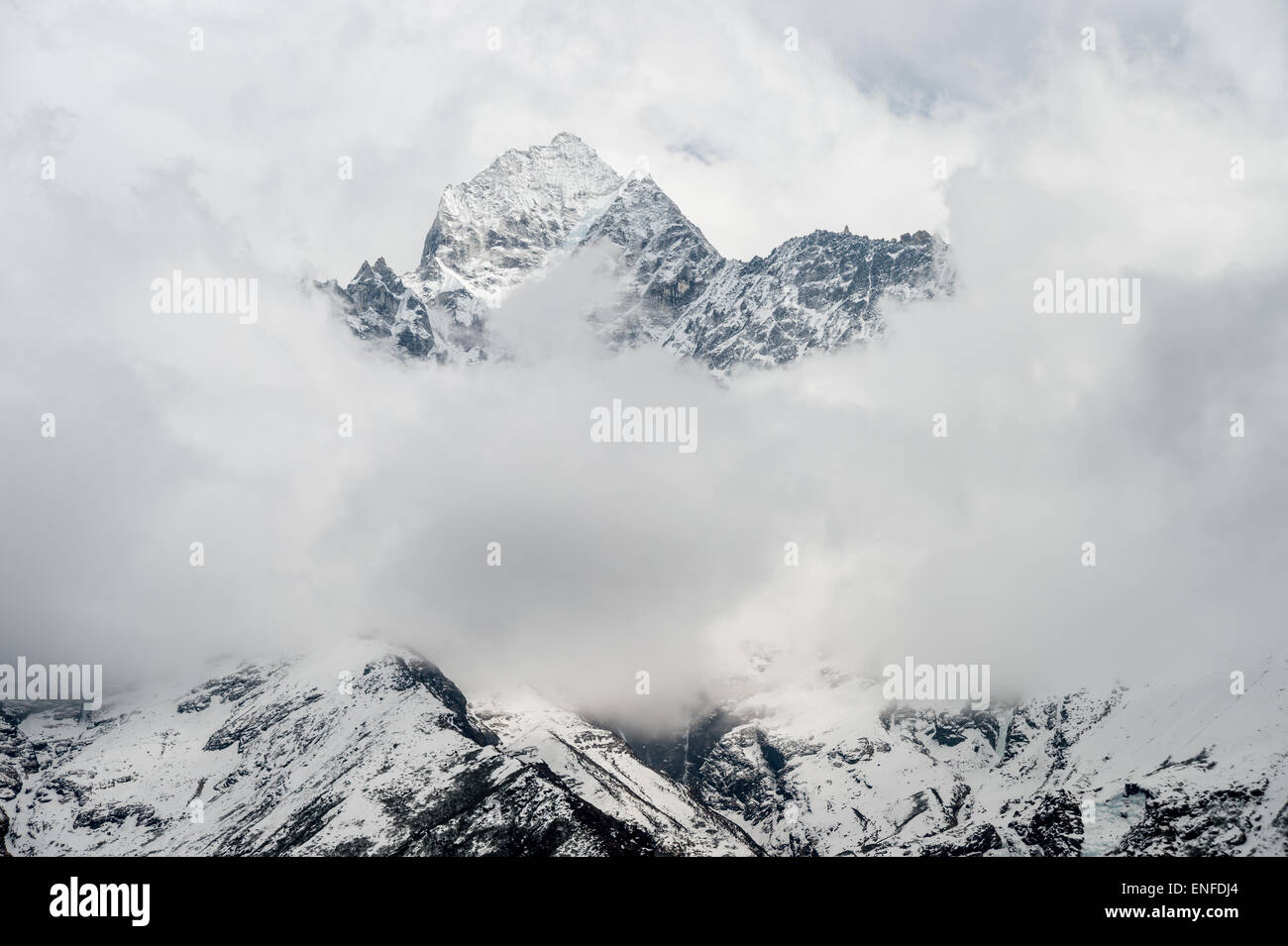 Himalayan summit emerging from the clouds in Nepal - Stock Image