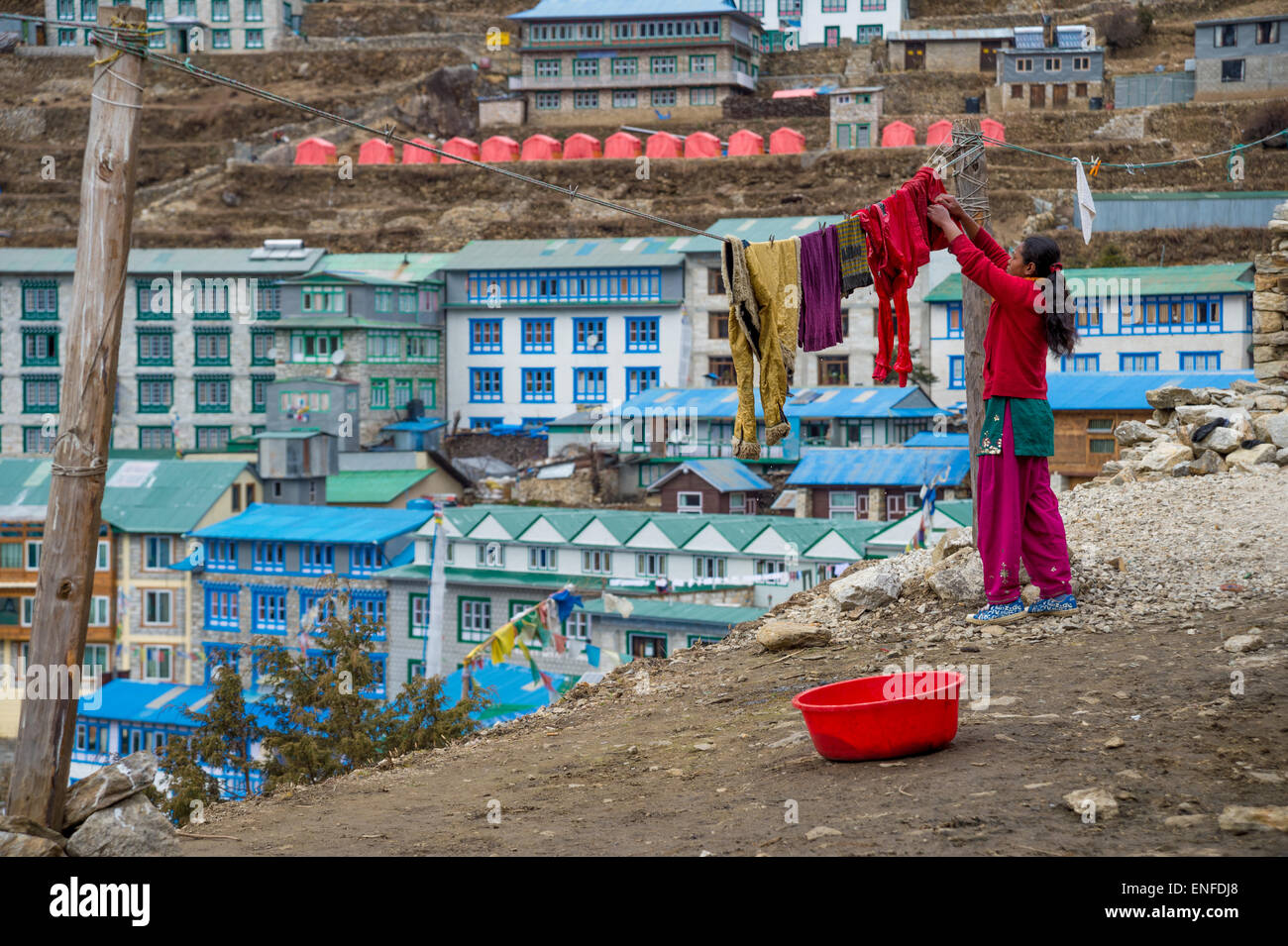 A Nepali woman hanging laundry on the washing line, in Namche Bazaar - Stock Image