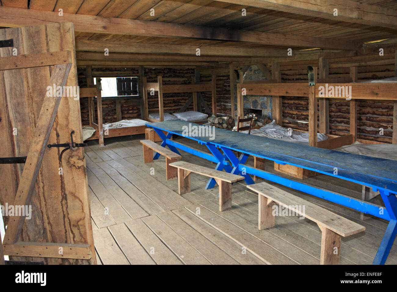 Blue table ,beds and furniture in the barracks at a Fort Loudoun State Park, historical French and Indian war site. - Stock Image