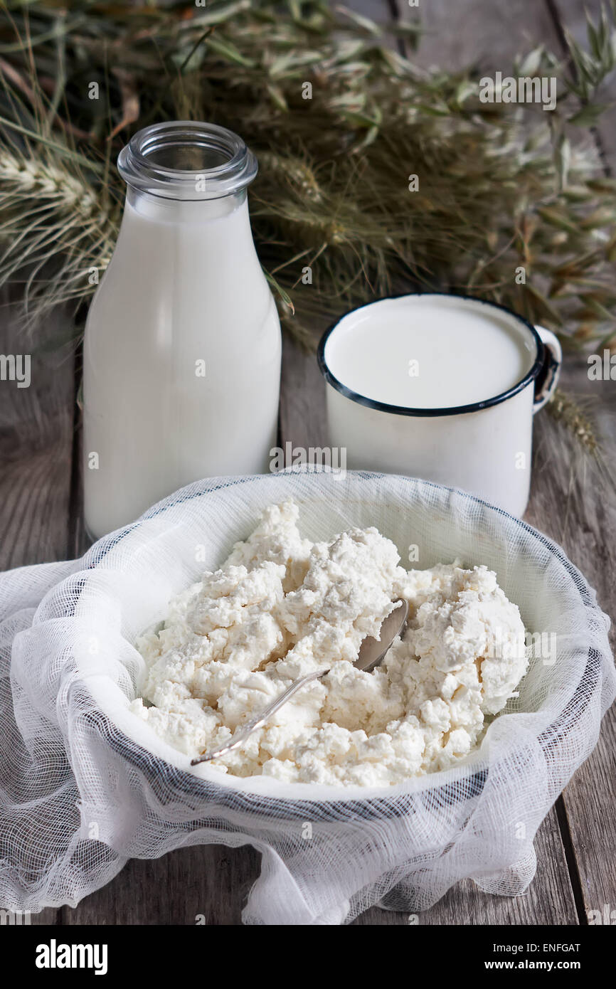 Milk, cottage cheese, wheat and oat grains on old wooden background. Concept of judaic holiday Shavuot. - Stock Image