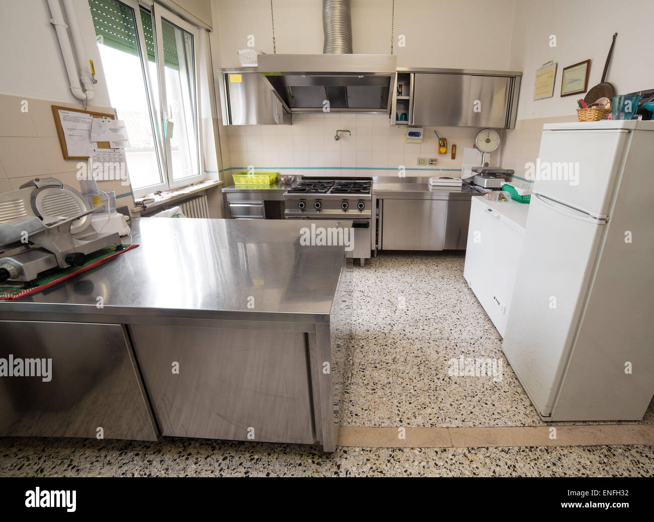 kitchen stainless steel industry with large gas stove and an industrial meat slicer Stock Photo