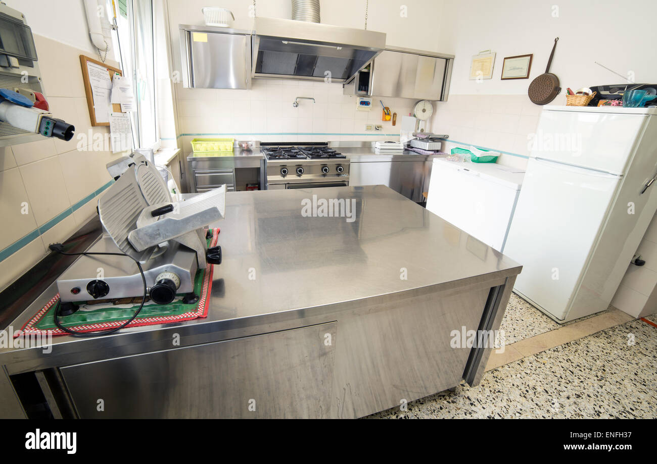 huge stainless steel kitchen with gas stove and an industrial meat slicer Stock Photo